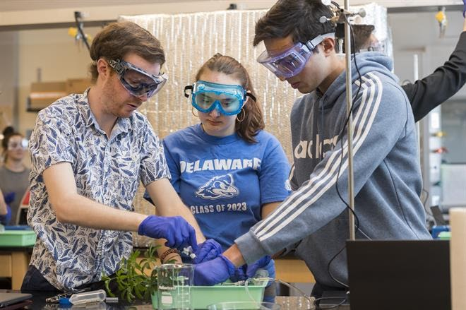 Three students work in a lab